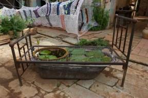 Cama de fierro, lavabo y tina de época con nenúfar , 2013.