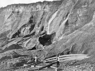 View of gold miners excavating an eroded bluff with jets of water at a placer mine in Dutch Flat, California, between 1857 and 1870.; from WikiMedia