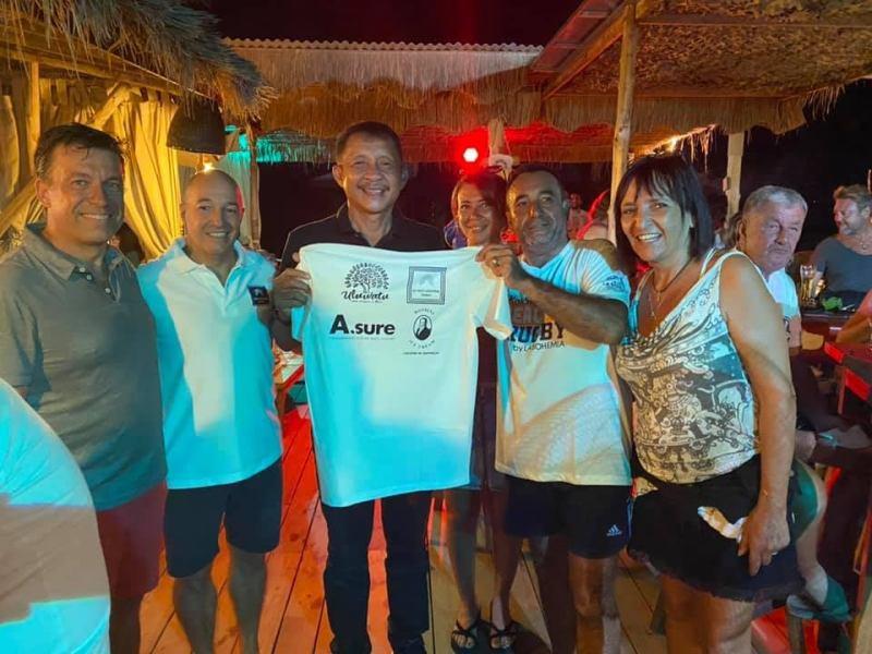 Monsieur le Maire de Koh Samui présentant avec Christophe Thiollet le t-shirt des sponsorts commerciaux. Soit Rossini Ice Cream, l'assurance  A.Sure, 3D Pest Control Samui et la boutique de décoration et de mobilier d'essence Balinaise Uluwatu.