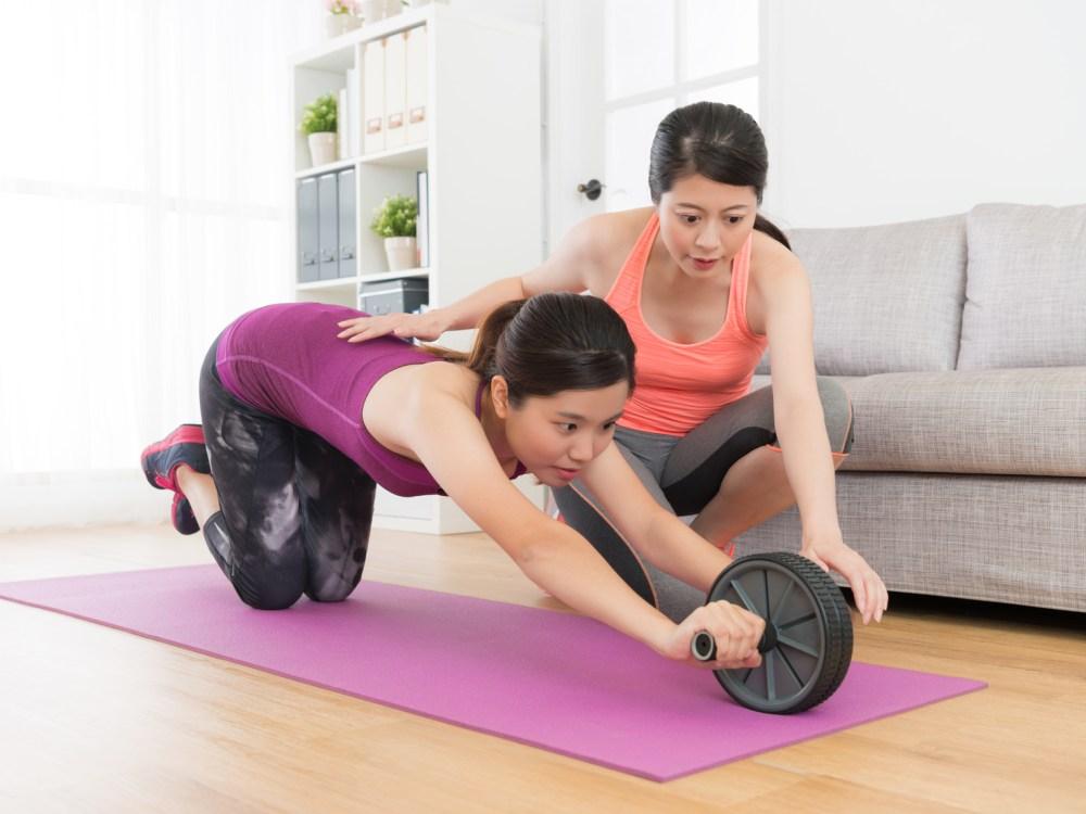 腹筋ローラーの使い方を学ぶ女性