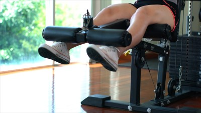 Legs of young sport girl doing seated leg curls on machine in gym