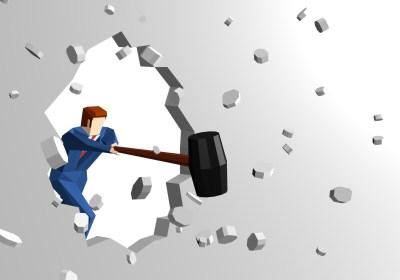 強度を確認するハンマーで壁を壊す男性