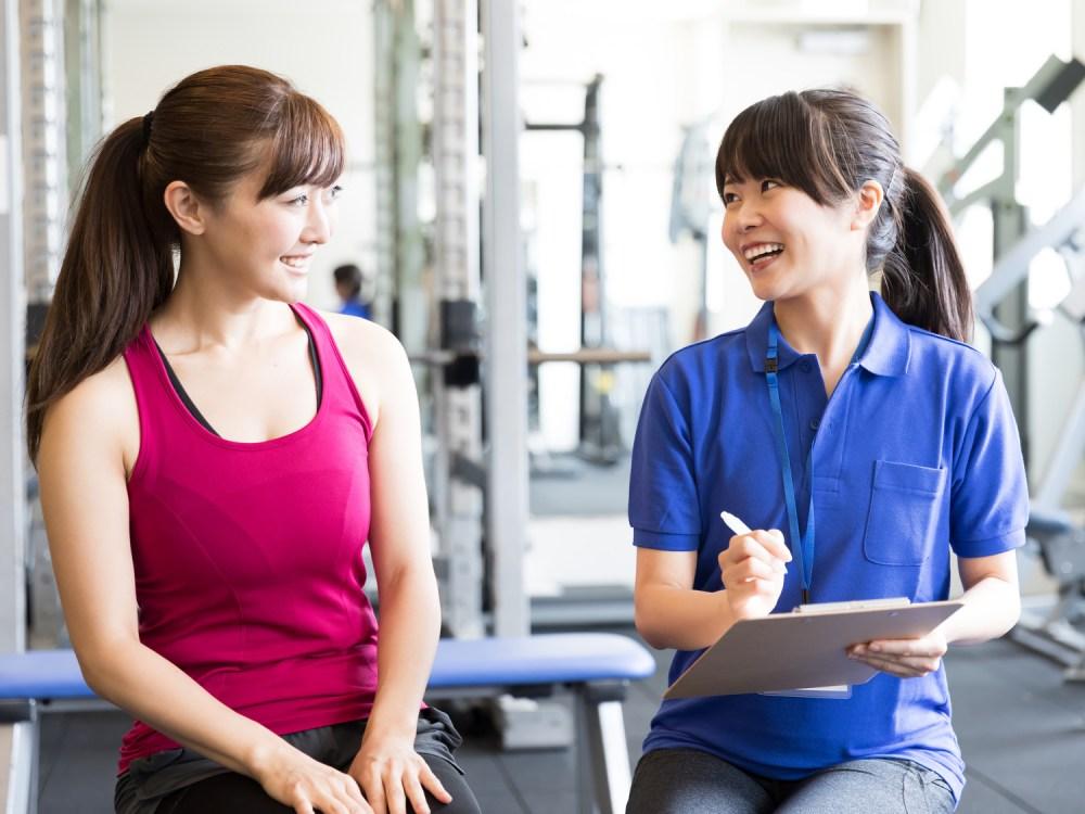 ジムでトレーナーとダイエットプログラムの相談をする女性