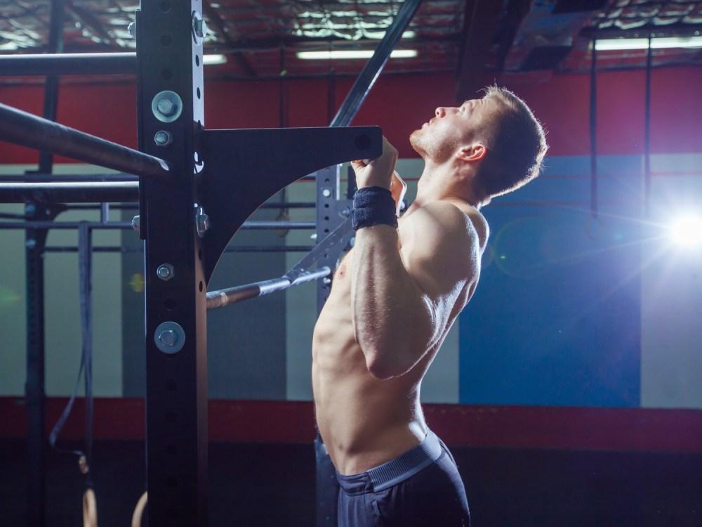 チンニングバーで懸垂をする男性