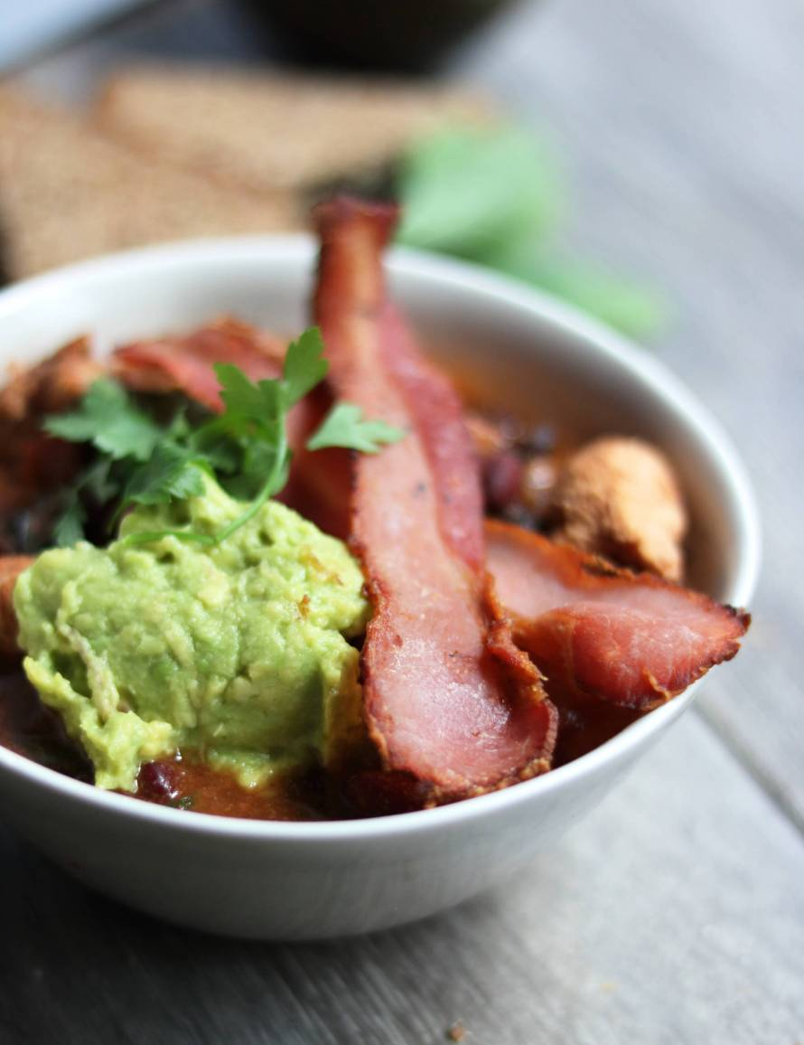 Smoky chicken and black bean stew with crispy bacon and guacamole