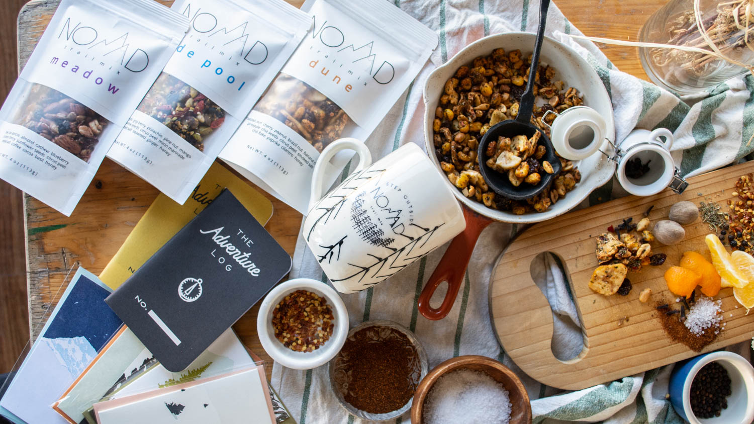 Nomad trail mix, coffee mug, notebooks, spread out on table.