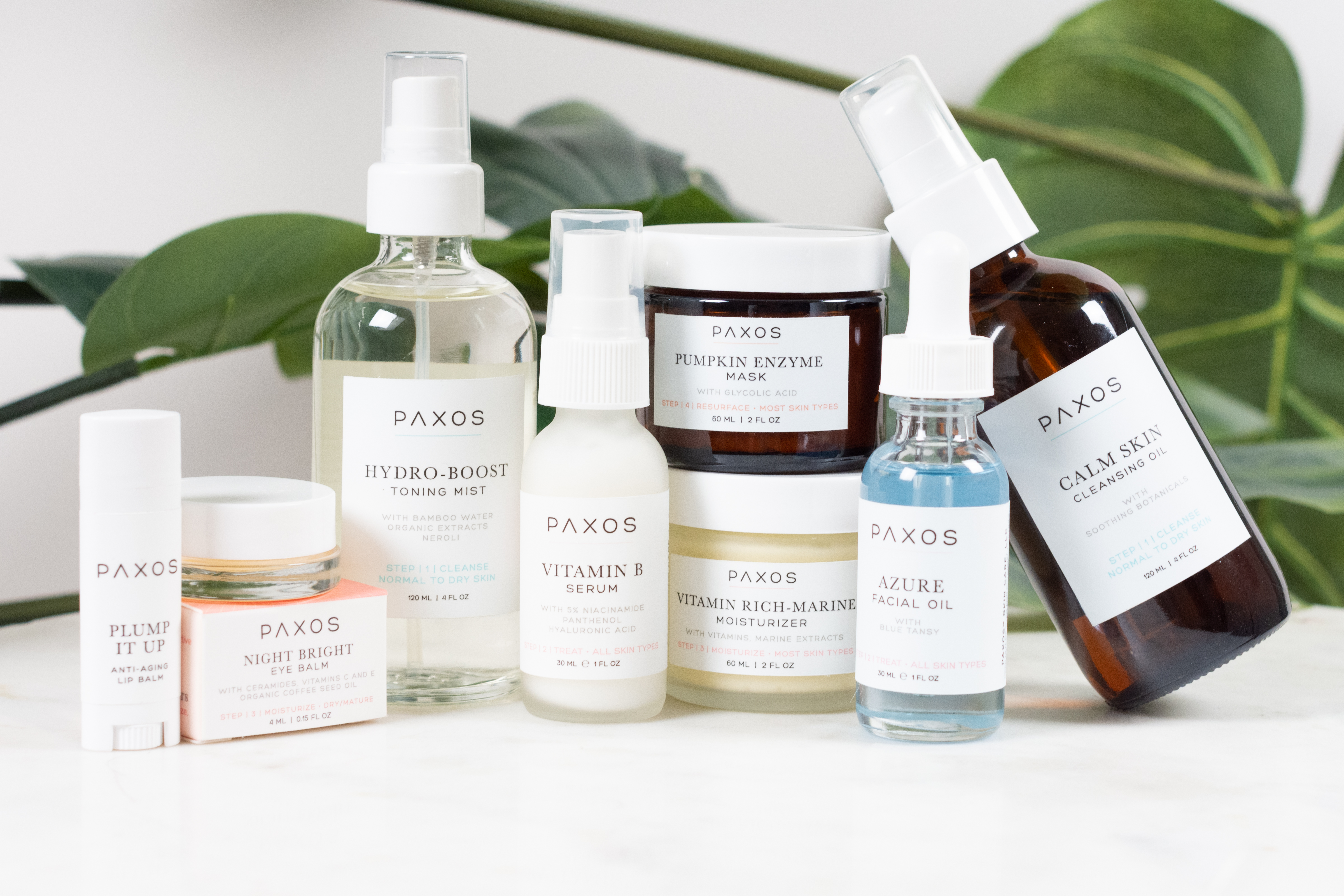 Skincare collection product photography on marble table with greenery background