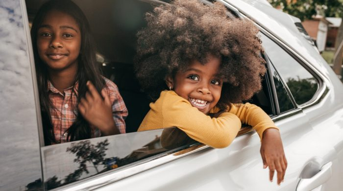 Two smiling kids leaning out of car window