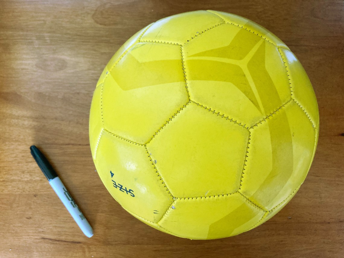 Yellow soccer ball with sharpie next to it
