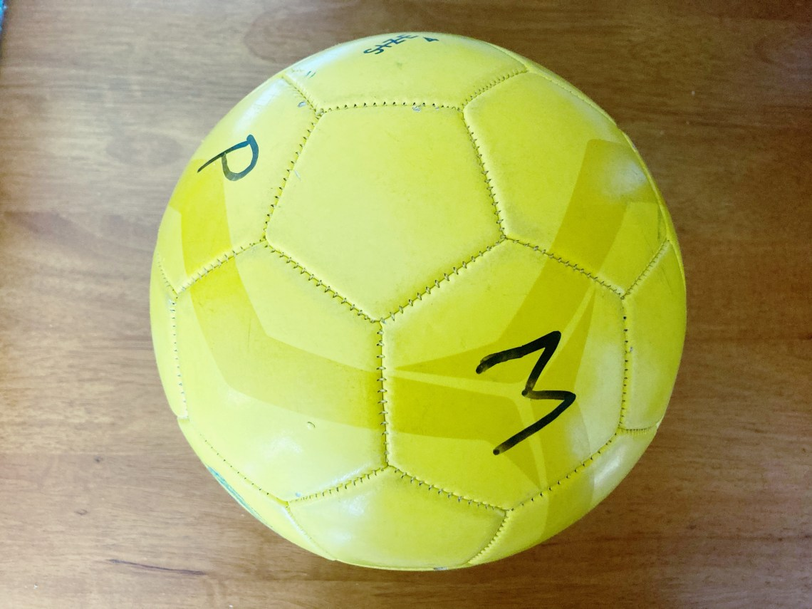 Yellow soccer ball with individual letters written on it