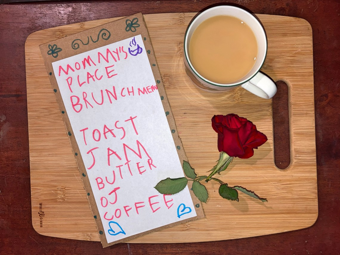 Cup of coffee, menu, and rose sitting on breakfast tray