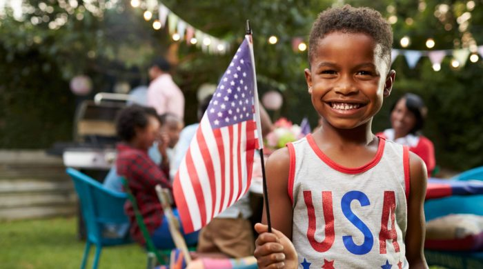 little boy holding American flag in USA shirt