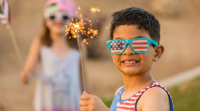 Little boy holding a sparkler wearing Fourth of July glasses and shirt