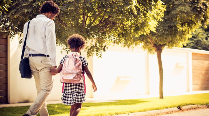 Father and daughter walk to school