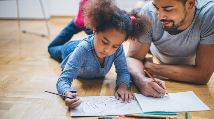Father and daughter color in a coloring book on the floor