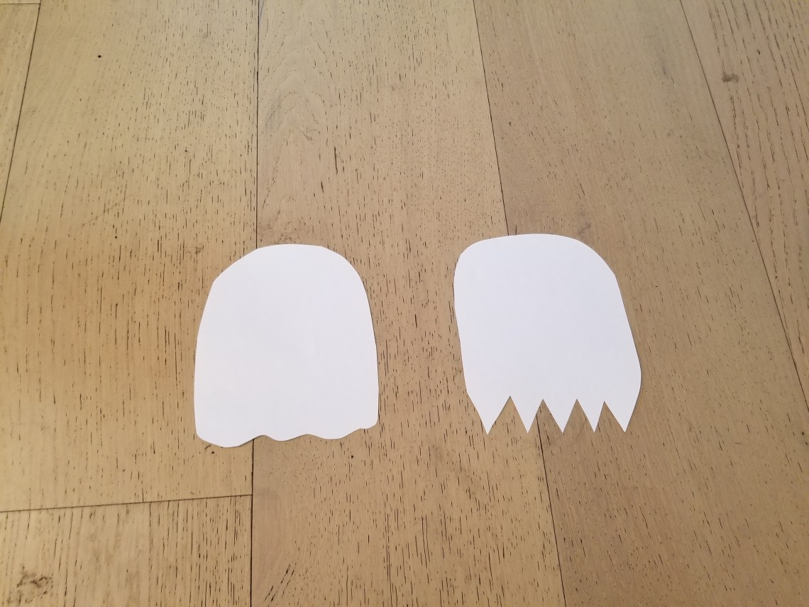 White paper cut into the shape of two ghosts