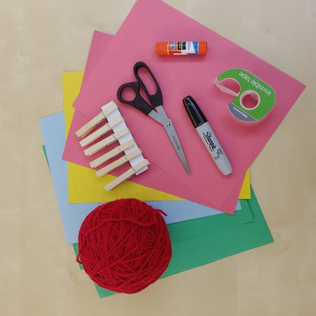 Yarn, scissors, tape, glue stick, Sharpie, construction paper, wooden clothespins