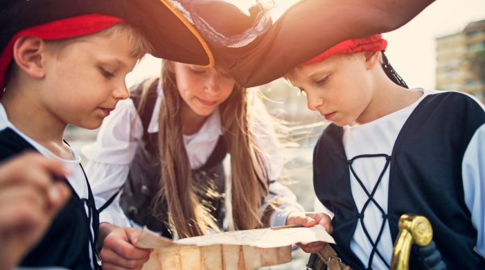 Three little kids playing pirates with a treasure map