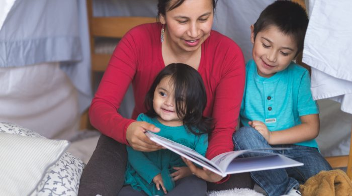 Mom reads picture book to two young children