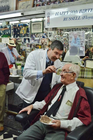 Floyd giving real barber, Russell Hiatt, a trim at his 90th birthday celebration in Mt. Airy, NC.