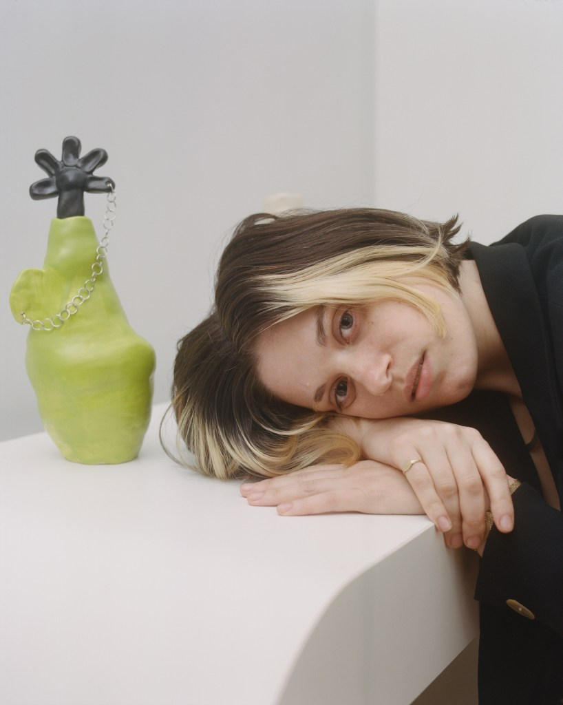 """Hayley rests her head on her arms atop a white table. Next to her is one of her ceramic vessels entitled """"i often mis-take my dreams for memories,"""" which is a lumpy bright lime green vessel with an ear-like handle. The handle is pierced and has a chain through it, which connects to a black ceramic flower petal that is atop it."""