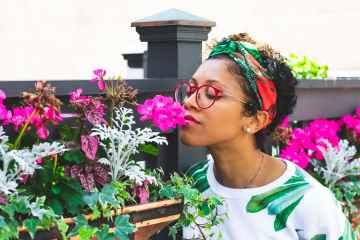 woman standing beside purple flowers