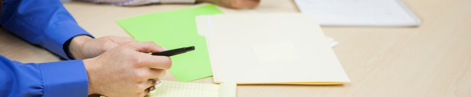Image of people in meeting writing on papers