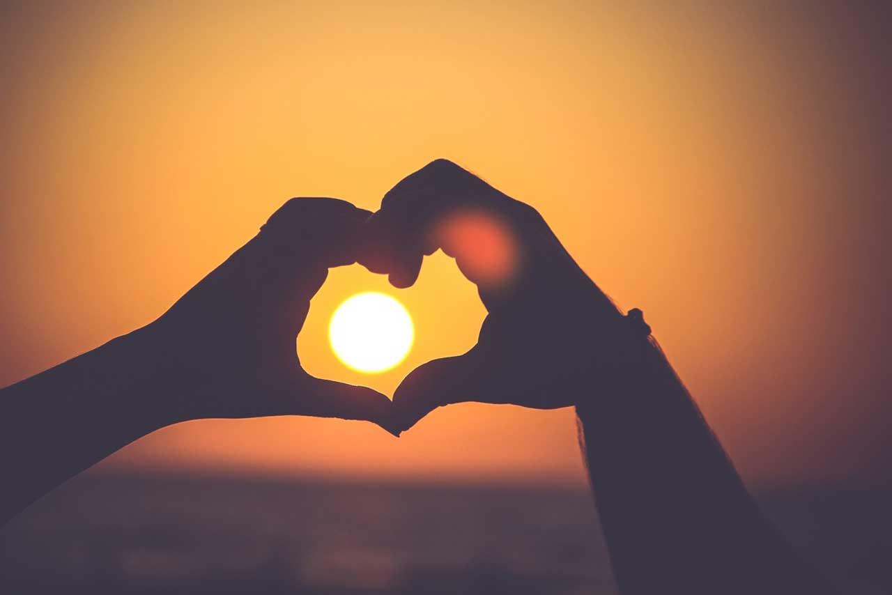 manos que forman un corazón con el sol dentro