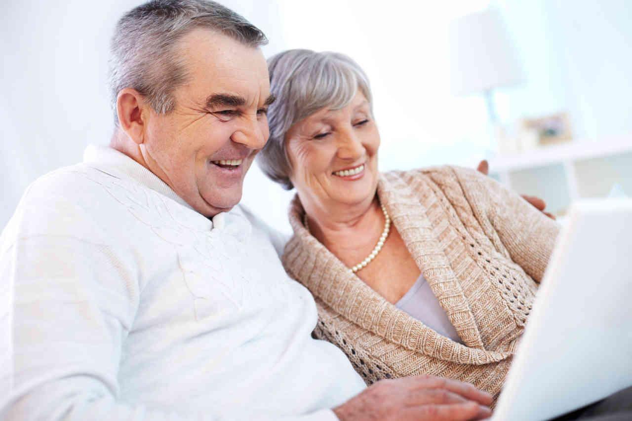 pareja adulta sentado frente a una notebook sonriendo