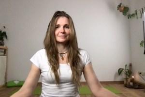 Frau sitzend im Meditationssitz im Zimmer mit einer Yogamatte im Hintergrund.