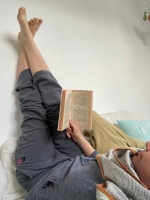 Frau liegend mit den Beinen hoch an der Wand, liest ein Buch