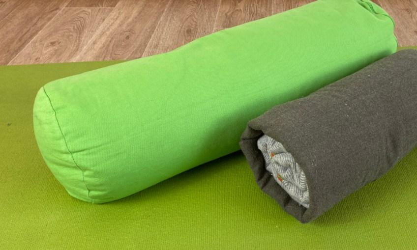 Ausschnitt Grüne Yogamatte auf Holzfußboden mit grünen Yoga-Bolster und zwei zusammengerollten Decken