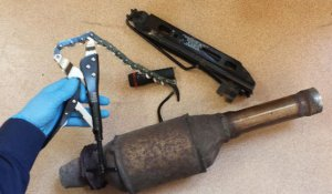 zdjęcie przedstawia wycięty katalizator samochodowy oraz narzędzia służące do jego wycięcia