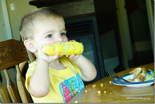 Little boy in yellow Tshirt chewing a cob of corn