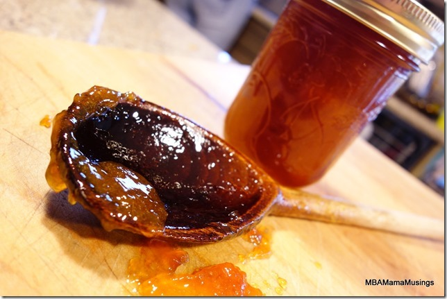 Spiced peach jam in a jar and a wooden spoon covered in jam