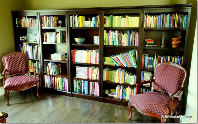 Wall of full bookshelves and two red arm chairs