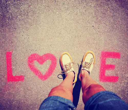 two feet making a sign for the letter V in the word love toned