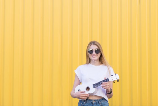 Happy, Cute Girl Plays Ukulele Against The Background Of A Yello