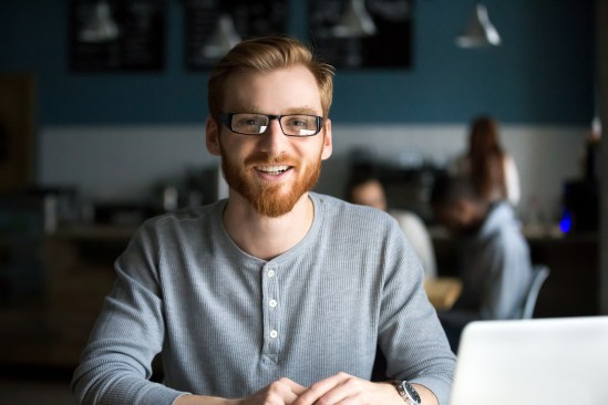 Smiling Redhead Man With Laptop Looking At Camera In Cafe, Happy