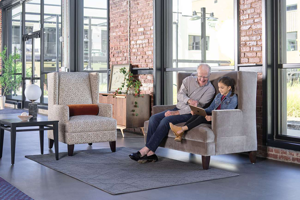 grandfather reading to granddaughter in senior living lobby