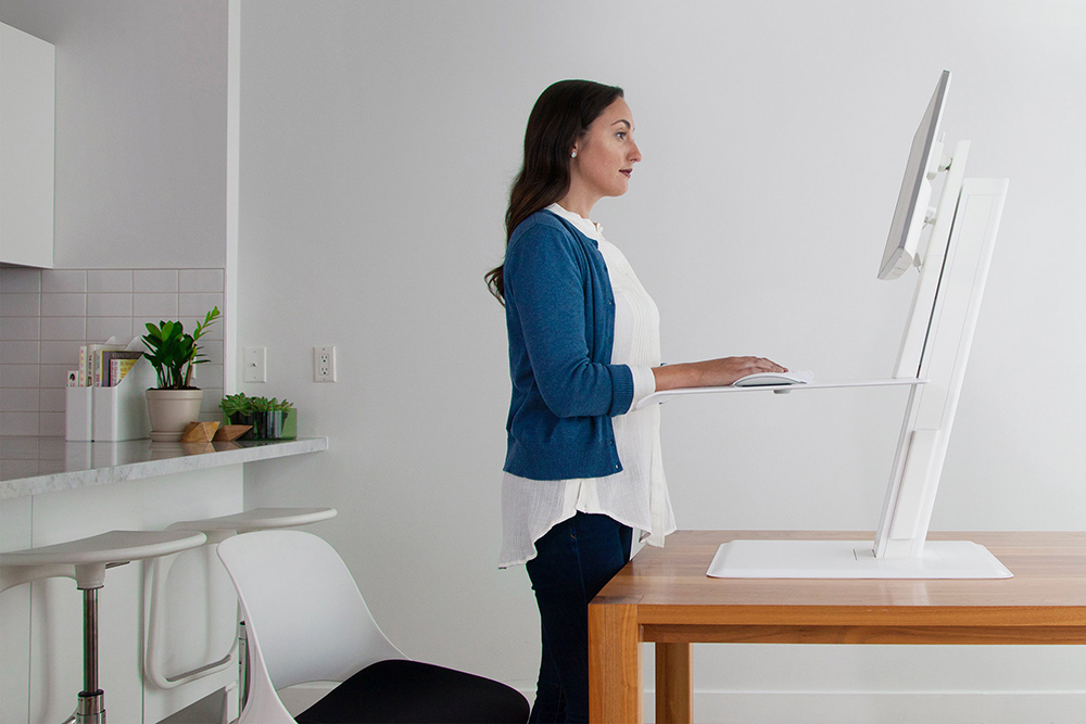 Lady in a blue sweater standing while working