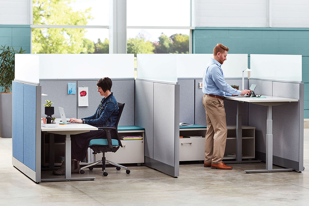 One person sitting to work and one standing