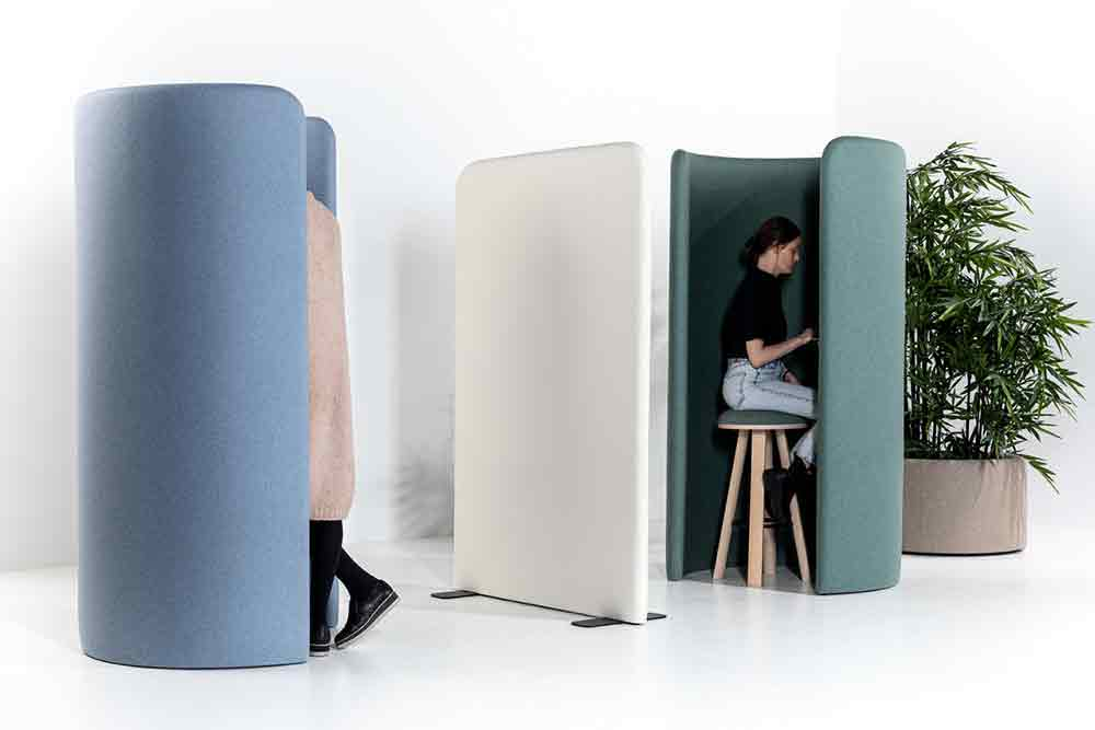 People in personal space pod booths