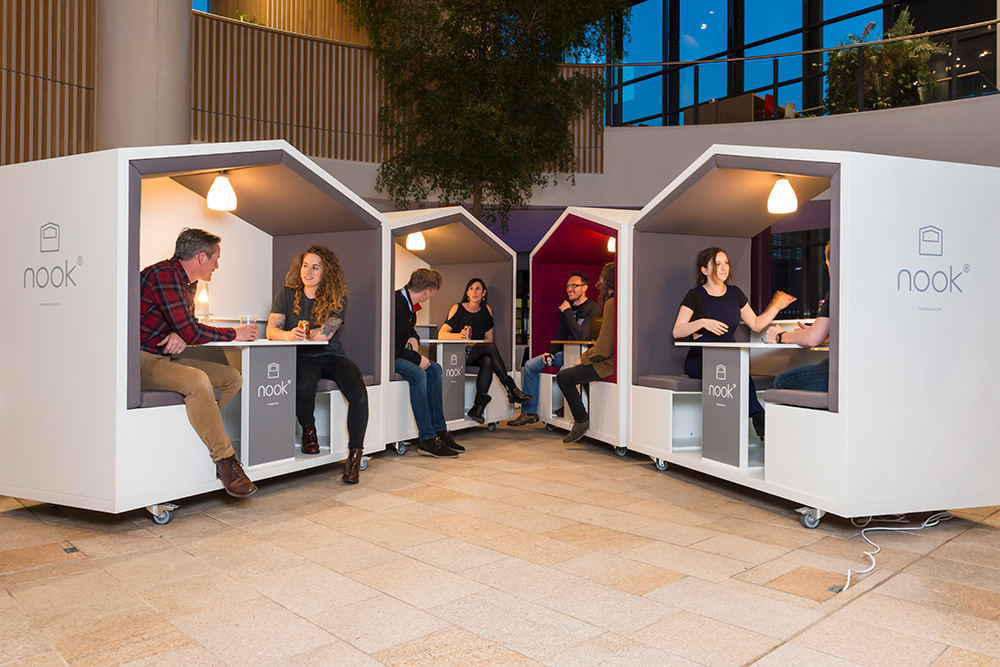 People sitting in enclosed pod spaces.