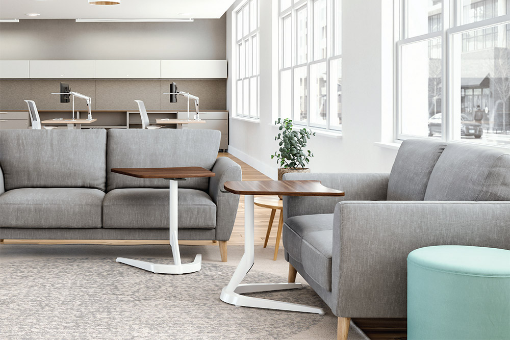 Portable work tables in office with sofas and desks.