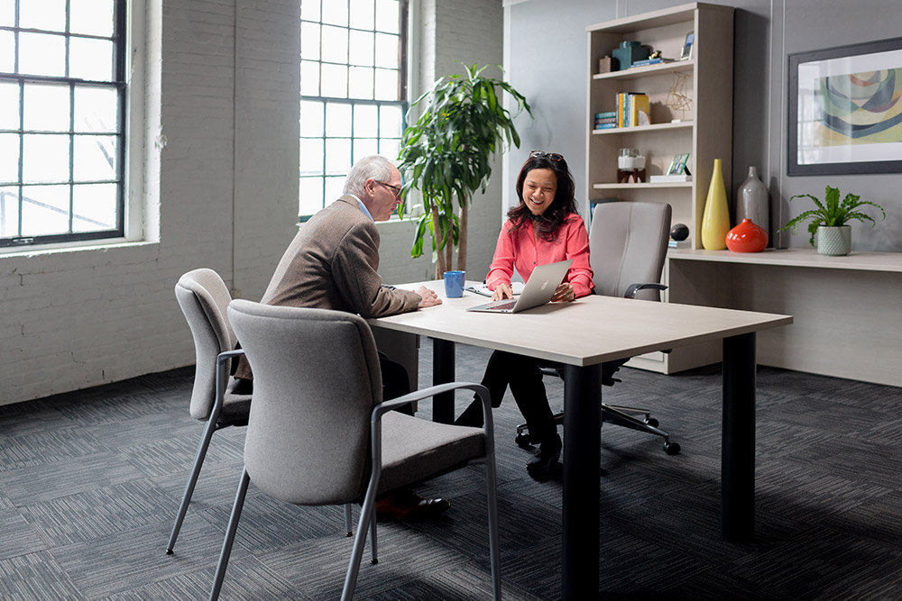 Two people sitting at office desk