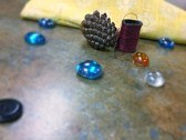 Marbles, pine and thread placed nicely in front of a beautiful yellow cloth.