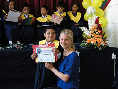 Renae Regehr poses with kindergarten graduate Ruth, who lives with her parents in prison in Bolivia. Renae and her husband Tyler are working with prison families in Bolivia, serving with MCC. The other children in the photo are Jocelyn, Luis Mario, Deymar, Brian, and Alejandra. Photo: MCC BC