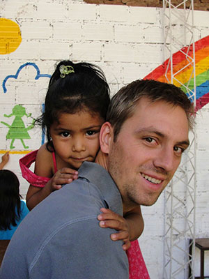 Tyler Regehr gets a hug from Carlita who lives with her parents in a prison in Bolivia. Tyler and his wife Renae are working with prison families in Bolivia, serving with MCC. Photo: MCC BC