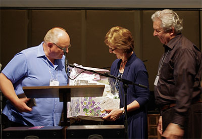 "Marilyn Hiebert receives a ""grandma"" gift from BC Moderator Ron van Akker as husband Rudy looks on. And, oh - something in an envelope."